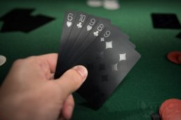 Man holding black playing cards while playing poker.