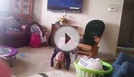 Little girl playing gymnastics at home